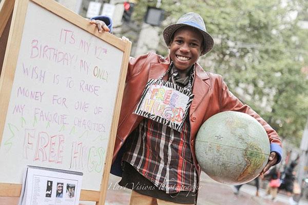 """この事件のデモ抗議に『フリーハグ』と書かれたプレートを持ち、デモに参加していた""""デボンテ・ハート少年(12)""""。"""