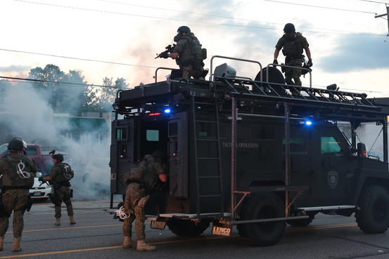 警察が装甲車を出動させ群衆にライフルを向けている画像