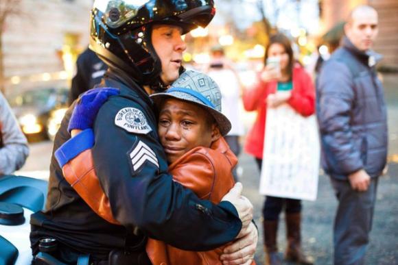 全米の心を打った1枚の写真、世界中でシェアされた黒人少年と白人警官のフリーハグ